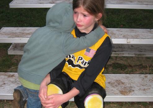 młodszy brat przytula płaczącą siostrę